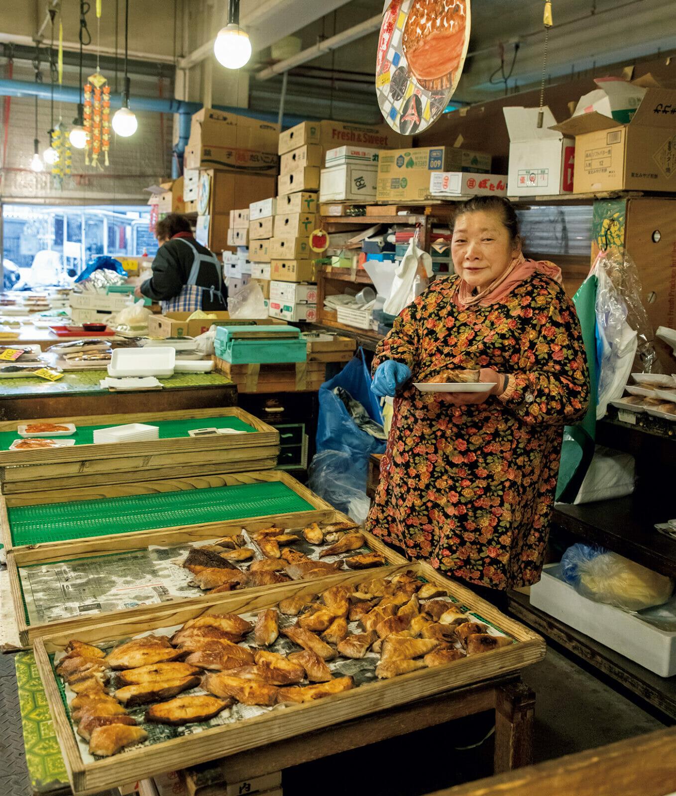 花柄のエプロンがかわいいカッチャ(お母さん)は〈八戸市営魚菜小売市場〉で、焼き魚を商う今商店の今富美子さん。オススメはカラスガレイ¥270とか。