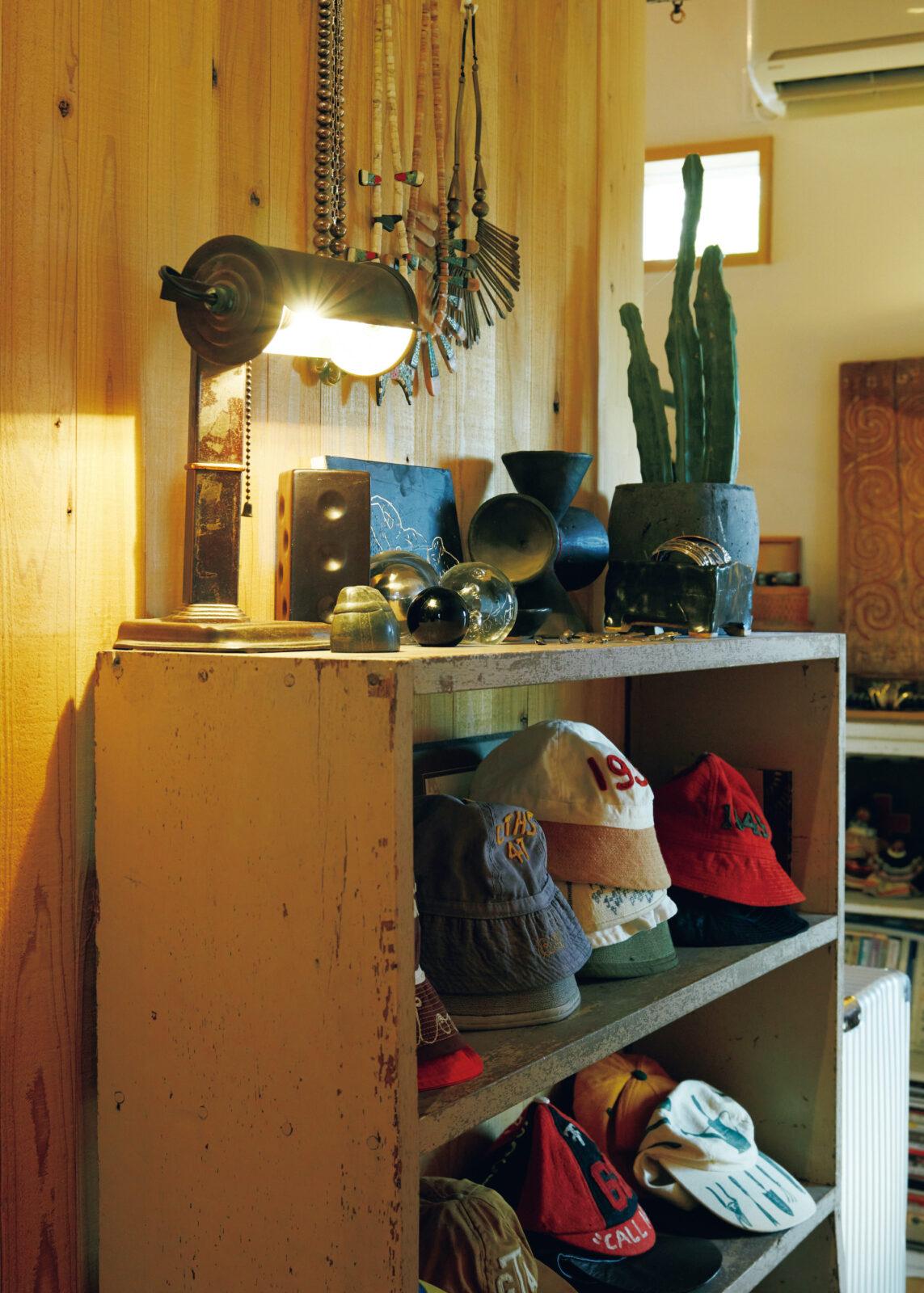 回廊の一角。古い靴箱に岩井さんが集めたヴィンテージのボーイスカウトハットやサイクリングハットがずらり。照明はロサンゼルスのアンティークモールで購入した。