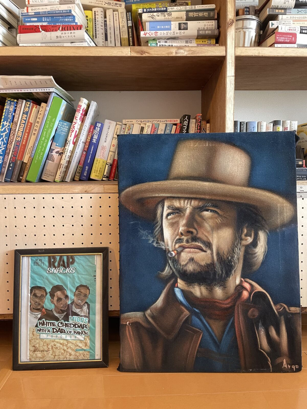 クリント・イーストウッドのヘタウマな絵画は、黒いベルベットに描かれた油絵。Argoとサインがあるが、ティファナに住んでいるという以外の詳細は不明。サイト「etsy」で購入。隣にあるのは、LAの路上で拾った「RAP SNACK」というアメリカにしか売られてないポテトチップスの袋。額装するといい感じ。