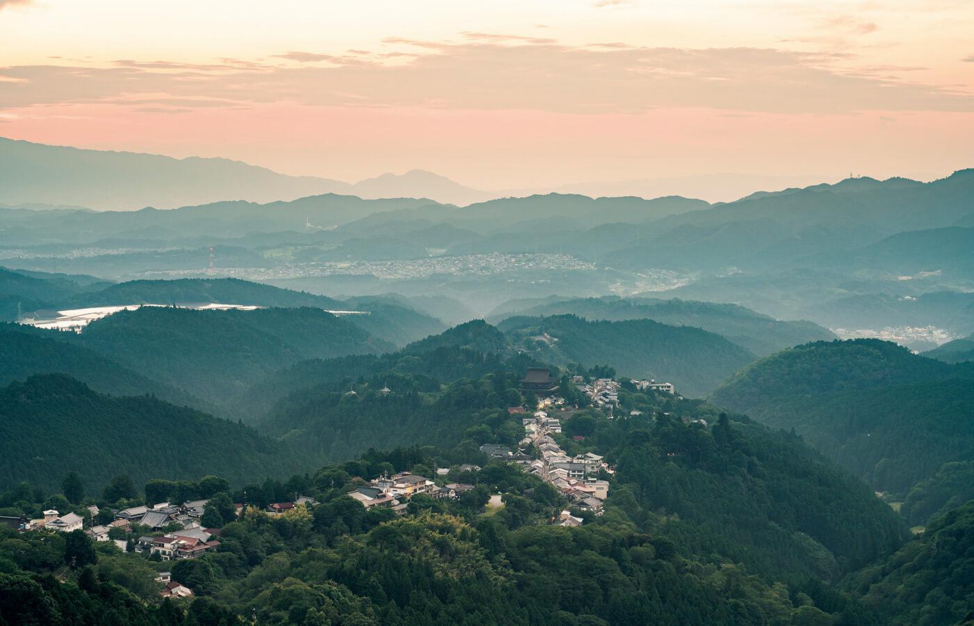 吉野山の花矢倉展望台から眺める夕景。遠くに連なる二上山、岩橋山、葛城山の山々からは、幽玄の美を感じる。春には山を桜色に染める様子が圧巻の、桜の名所としても名高い吉野山を上から望む絶景ポイントでもある。