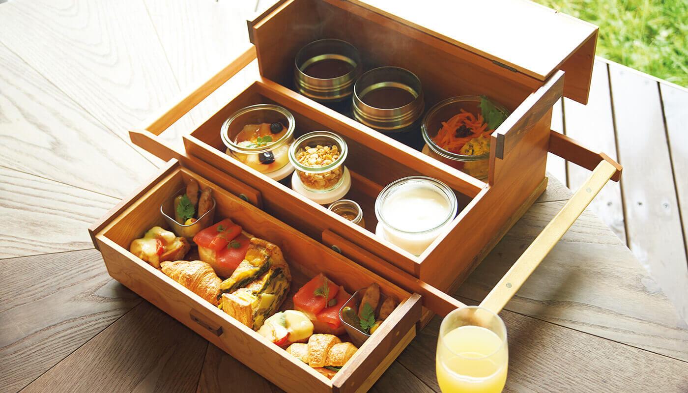 〈星野リゾート奥入瀬渓流ホテル〉の翌朝はボックスに入ったキッシュやスープなどの「渓流テラス朝食」でピクニック気分を満喫。5月~10月の期間限定。
