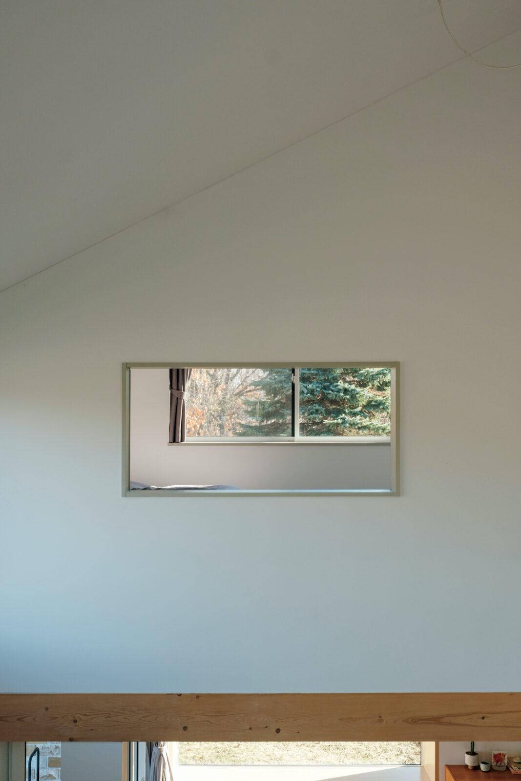 2階のゲストルームから、吹き抜けを通して対面の寝室を見る。天井に天窓を開けようかと迷ったが、「開けなくてよかった。真っ白な天井が景色を生かしているなあ、と実感しています」。