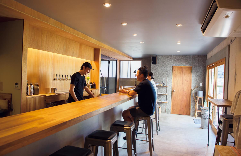 店主の古沢さん。タップルームのガラス戸越しに醸造室が眺められる。カウンターのほかテーブル席、立ち飲み、外飲み席も。