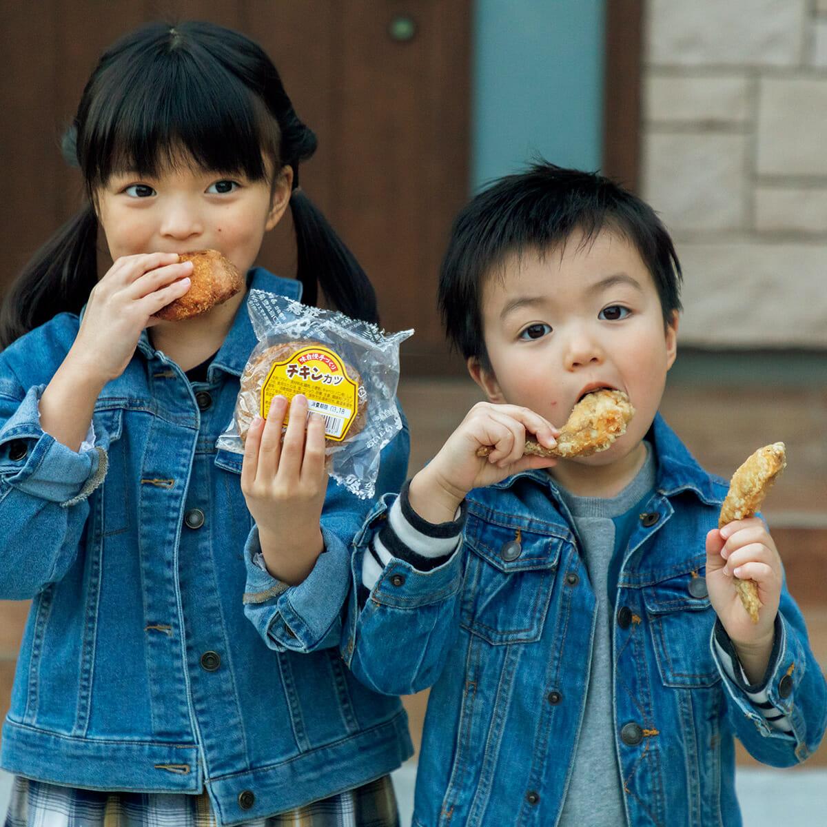 女の子が持っているのが、八戸を代表するB級グルメ〈むつ食品〉のチキンカツ。男の子が食べているのは〈館鼻岸壁朝市〉でも大人気の〈大安食堂〉のしおてば。
