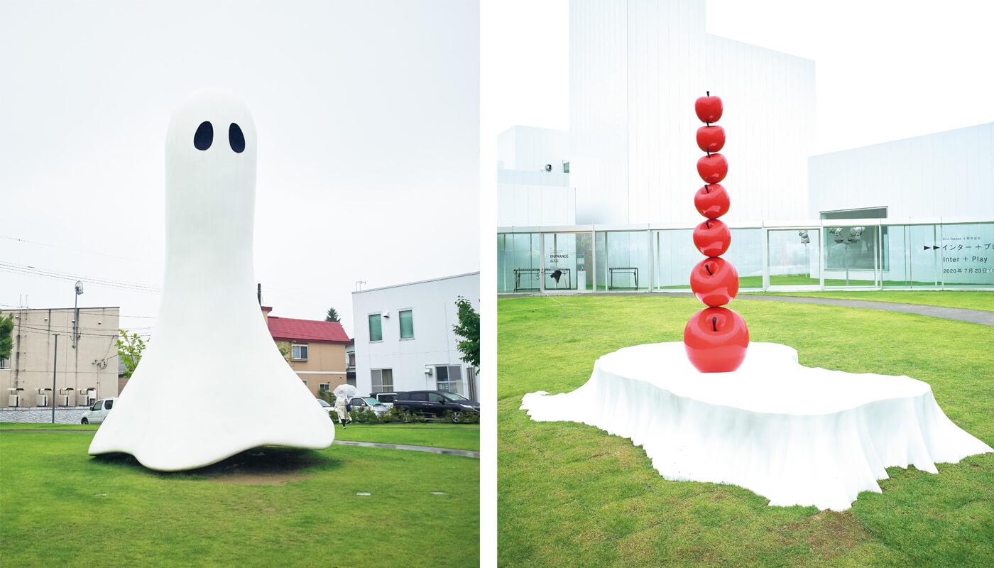 〈十和田市現代美術館〉の屋外に設置されたリンゴのオブジェは、『Arts Towada十周年記念「インター+プレイ」展』の鈴木康広《はじまりの果実》。左はインゲス・イデーの《ゴースト》。住所:十和田市西二番町10-9   地図