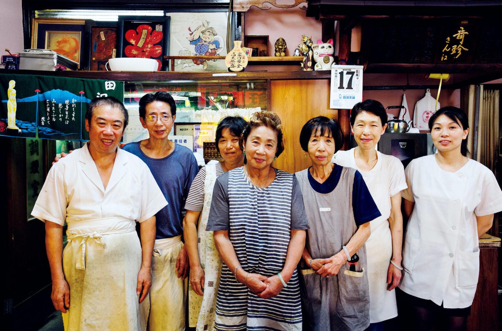 左から2番目が料理長・黄国栄さん。中央に立つ黄秀晃さんは厨房を、右隣の黄秀輿さんがフロアを仕切る。料理長の妻やスタッフたちも集合。