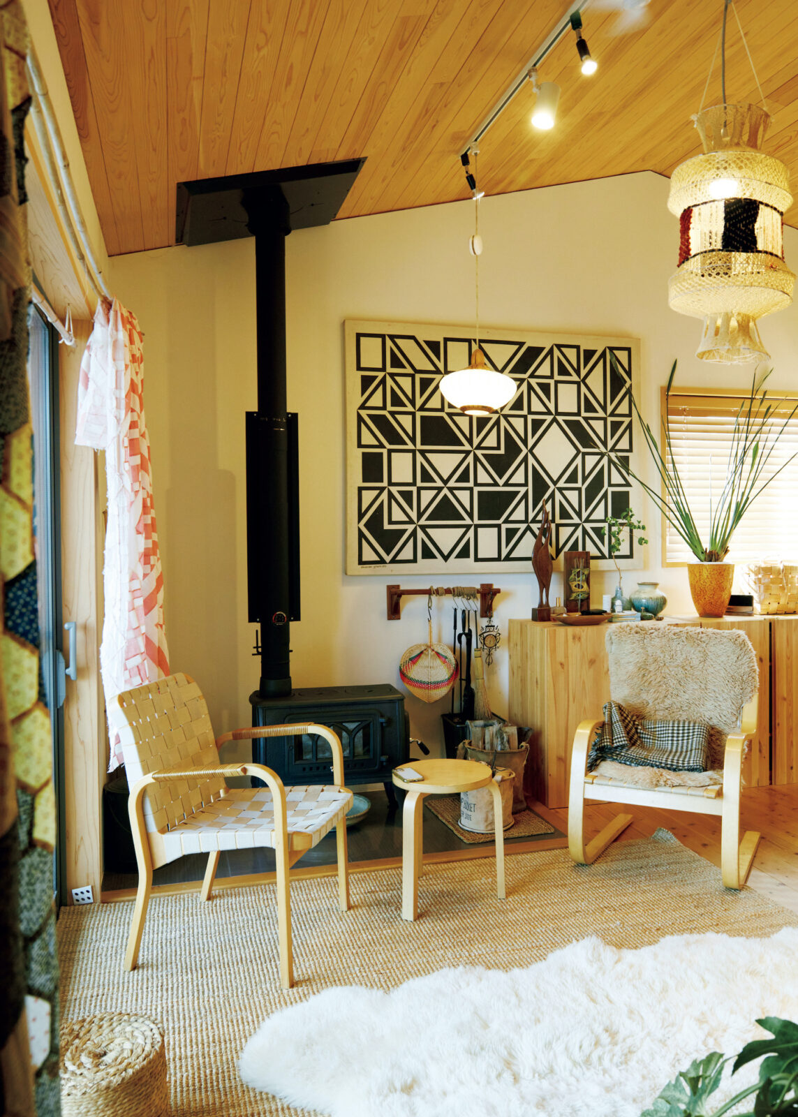 カーテンは庭に生えていた竹に、ヴィンテージのキルトをかけて設えた。壁の絵は名古屋のインテリアショップ〈パームスプリングス〉で購入したアレキサンダー・ジラード。
