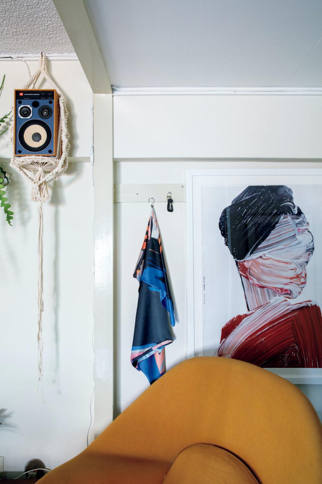 玄関横の壁まわり。ポスターは武田鉄平。壁に掛けたシルクスカーフには小澤雅志のペイントが施されている。左上のJBLのスピーカーは天井から吊すため、元職場の先輩で〈ウッドアンドノット〉の小野正史にマクラメ編みを頼んだ。