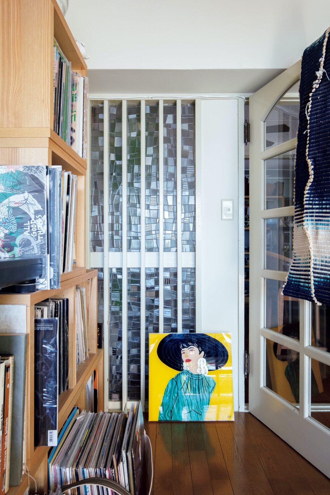 リビングとダイニングを隔てる白い扉と格子のすりガラスはこの部屋オリジナル。その意匠は今の時代も新鮮で、家具選びの指針になったという。足元に置かれたビビッドな婦人の絵は、友人のアーティスト、アズサイイダのもの。