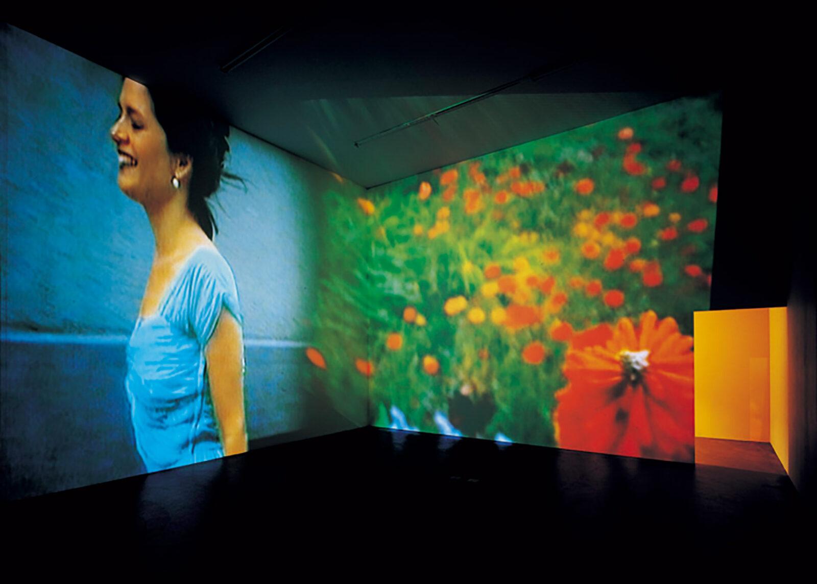 《永遠は終わった、永遠はあらゆる場所に》1997年  ヴェネチア・ビエンナーレ若手作家部門賞受賞。コーナーの壁一枚に花形のハンマーで車の窓ガラスを割る女性、もう一枚には花が投影される。実はビヨンセのMVのパロディでジェンダーやフェミニズムについて問うている。  京都国立近代美術館蔵 Photo by Alexander Trohler