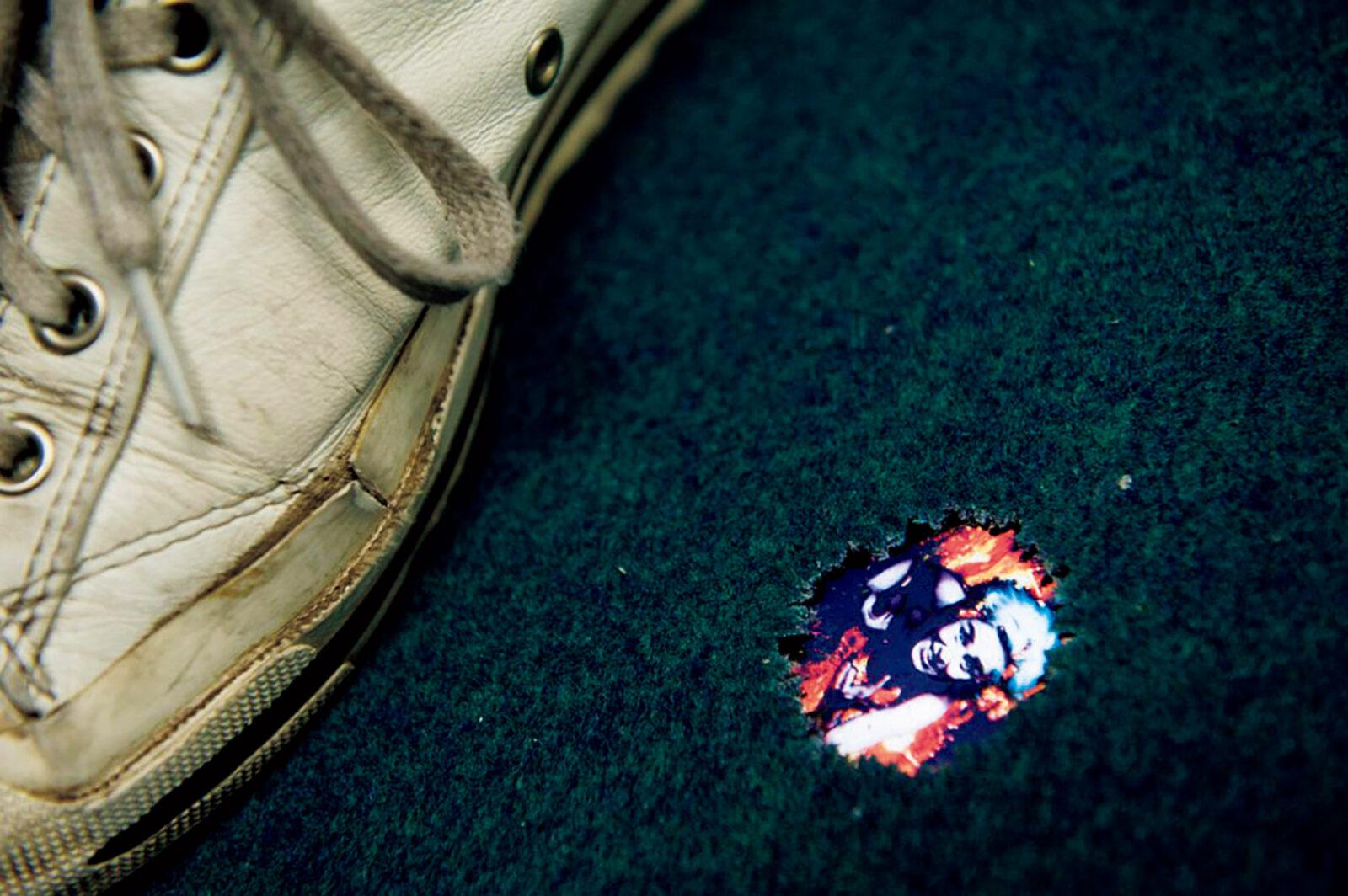《溶岩の坩堝でわれを忘れて》1994年  1997年からMoMA PS−1で継続的に公開されている初期短編ビデオ作品の一つ。画面にはリスト自身が映り、両手を伸ばして助けを求めている。作品を見るために、床に開いた小さな穴を覗き込む必要がある。  ヘイワードギャラリーでの展示風景 Photo: Linda Nylind