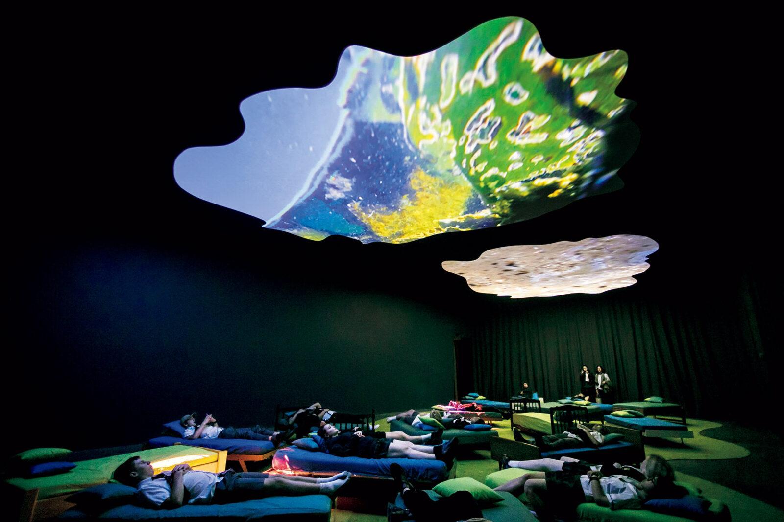 《4階から穏やかさへ向かって》2016年  「まるでモネの《睡蓮》を水の下側から見たような景色」が広がっていたという、ライン川の水中で撮影された断片的な映像。デンマークのテキスタイルメーカーKvadratのテキスタイルに覆われたベッドに横たわり鑑賞。  オーストラリア現代美術館での展示風景 Photo: Anna Kucera