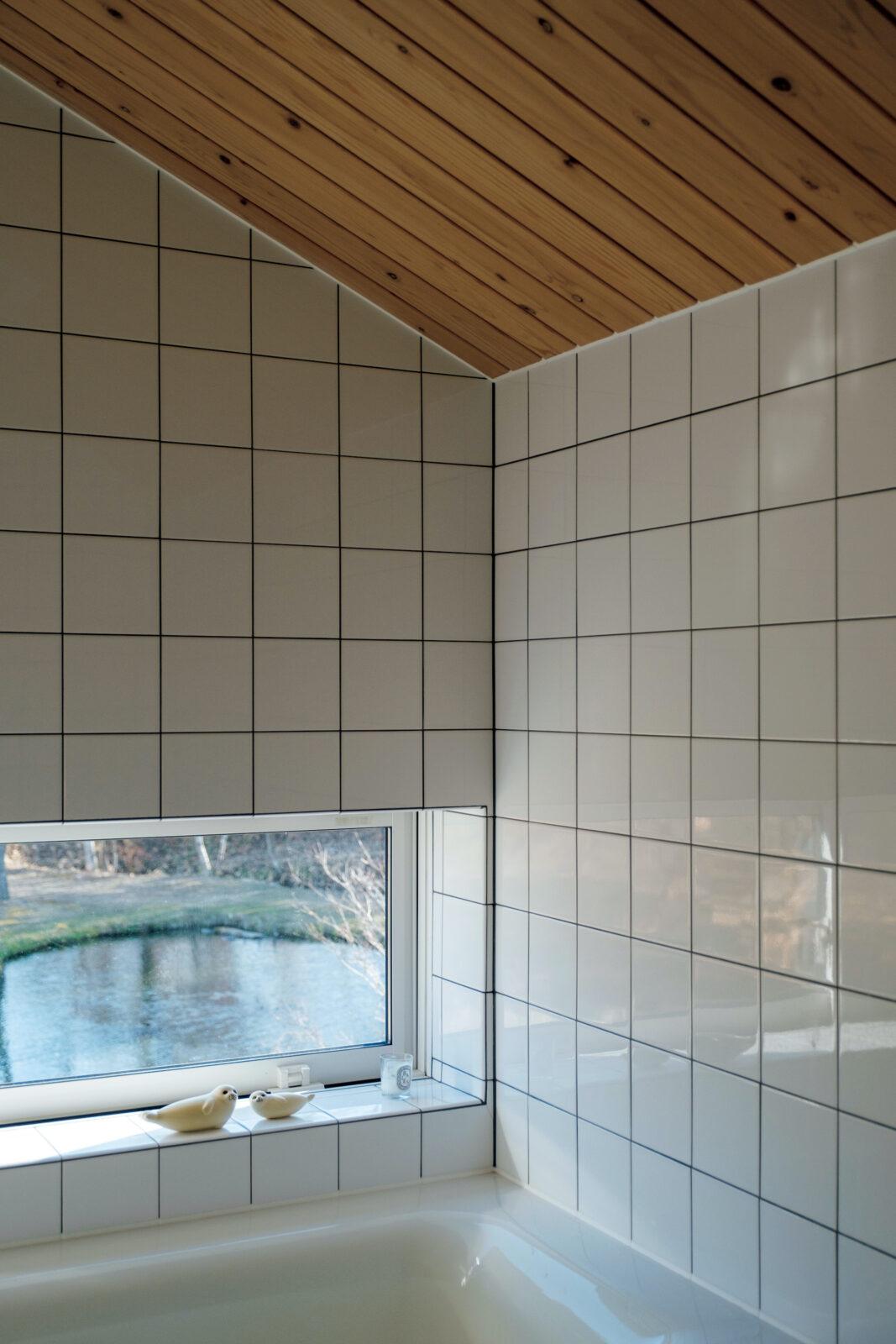 """2階のバスルームの窓からも池が見える。お風呂は温泉""""かもしれない""""地下水を沸かして使用。窓辺の陶器のオブジェは、リサ・ラーソン。北の家には北欧のデザインがよく似合う。"""