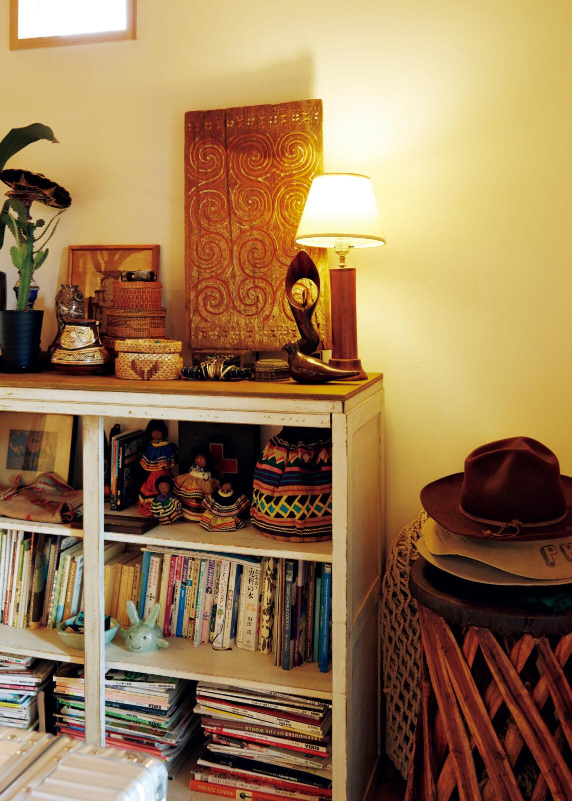 古い食器棚を回廊に置き、本を並べる。棚の中のカラフルな人形はフロリダのセミノール族のもの。壁に立てかけたアフリカのウッドワークは名古屋の古着屋で手に入れた。