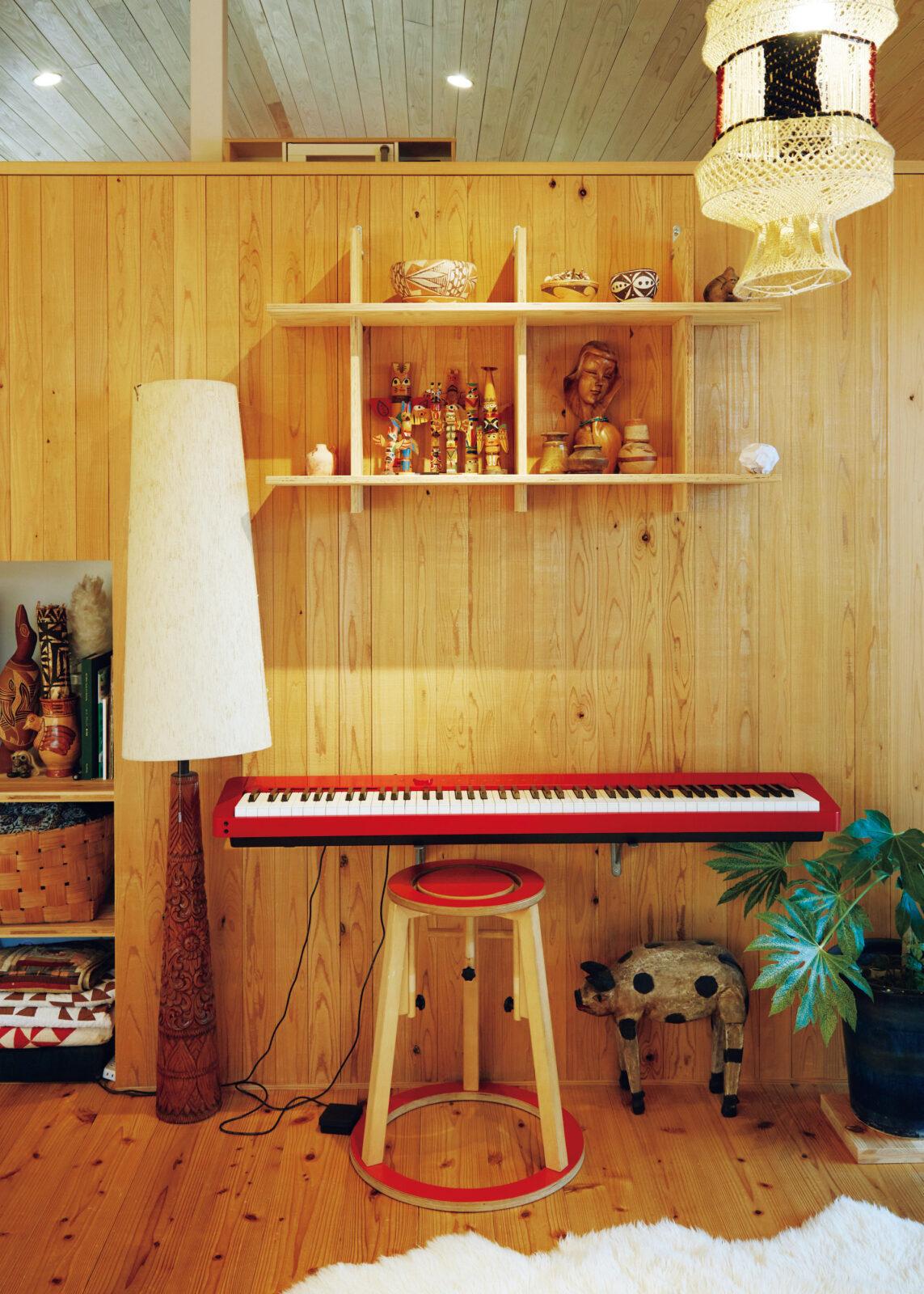 リビングの壁。2年前に娘が始めたピアノを設置したところ、家にあったセイミ社の椅子と色味がマッチ。飾り棚にはトーテムポールなど、アメリカやメキシコのフォークアートが並ぶ。