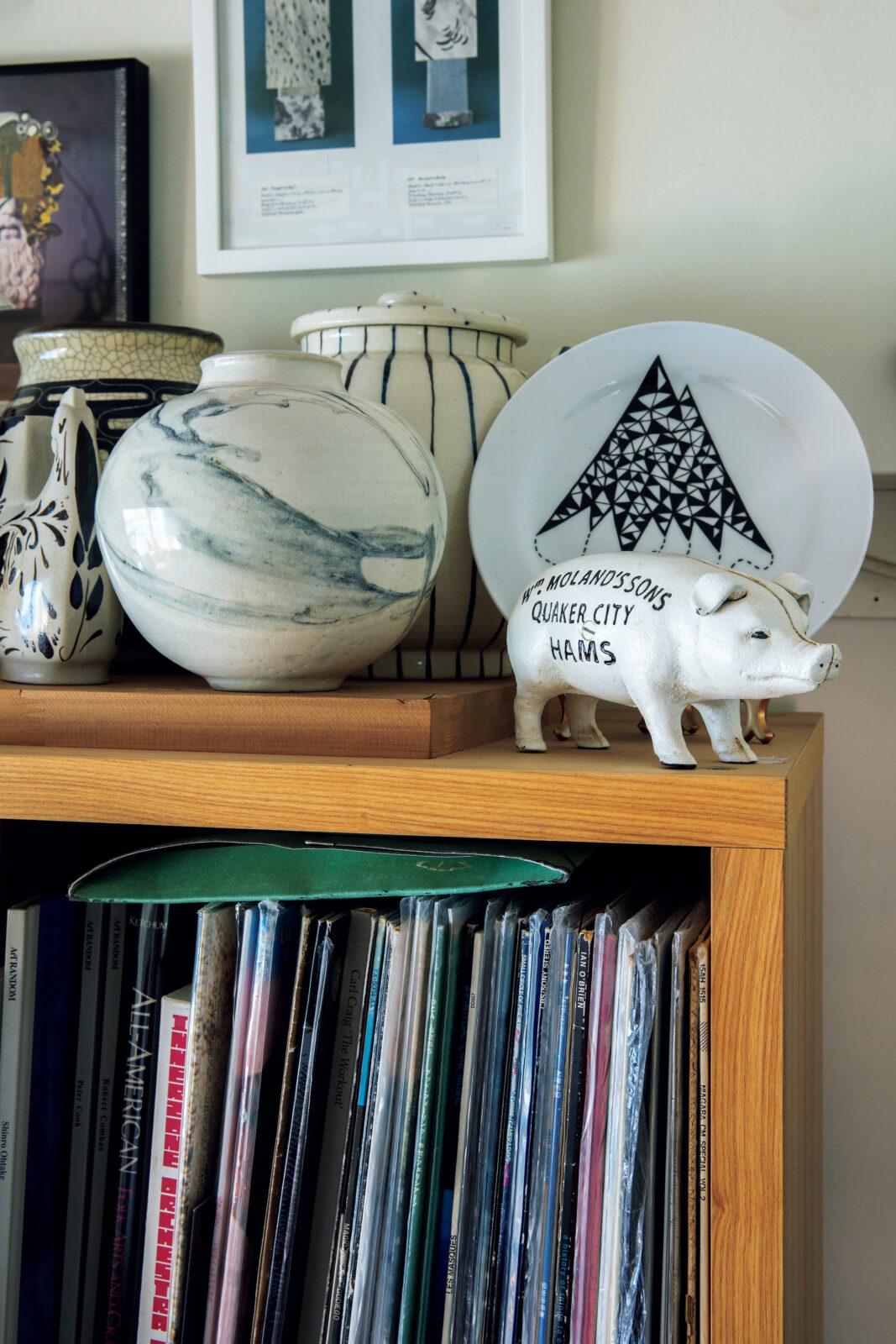 リビングのレコード棚右上は白を集めた一角に。豚の貯金箱は、かつてアメリカの精肉店で配られていたノベルティのレプリカ。後ろに立てかけた平皿は神山隆二。マーブル柄のように釉薬が入った白い壺は靖国神社で行われていた骨董市で。