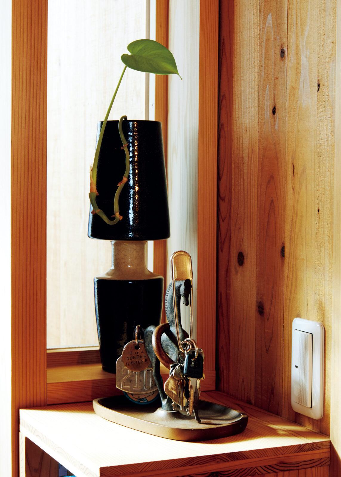 玄関横、シューズボックスの上。大須観音骨董市で購入した花瓶に、庭に生えていたグリーンを生けた。キーホルダーの引っ掛かりが計算されたブロンズの馬のオブジェも同じ骨董市で入手。