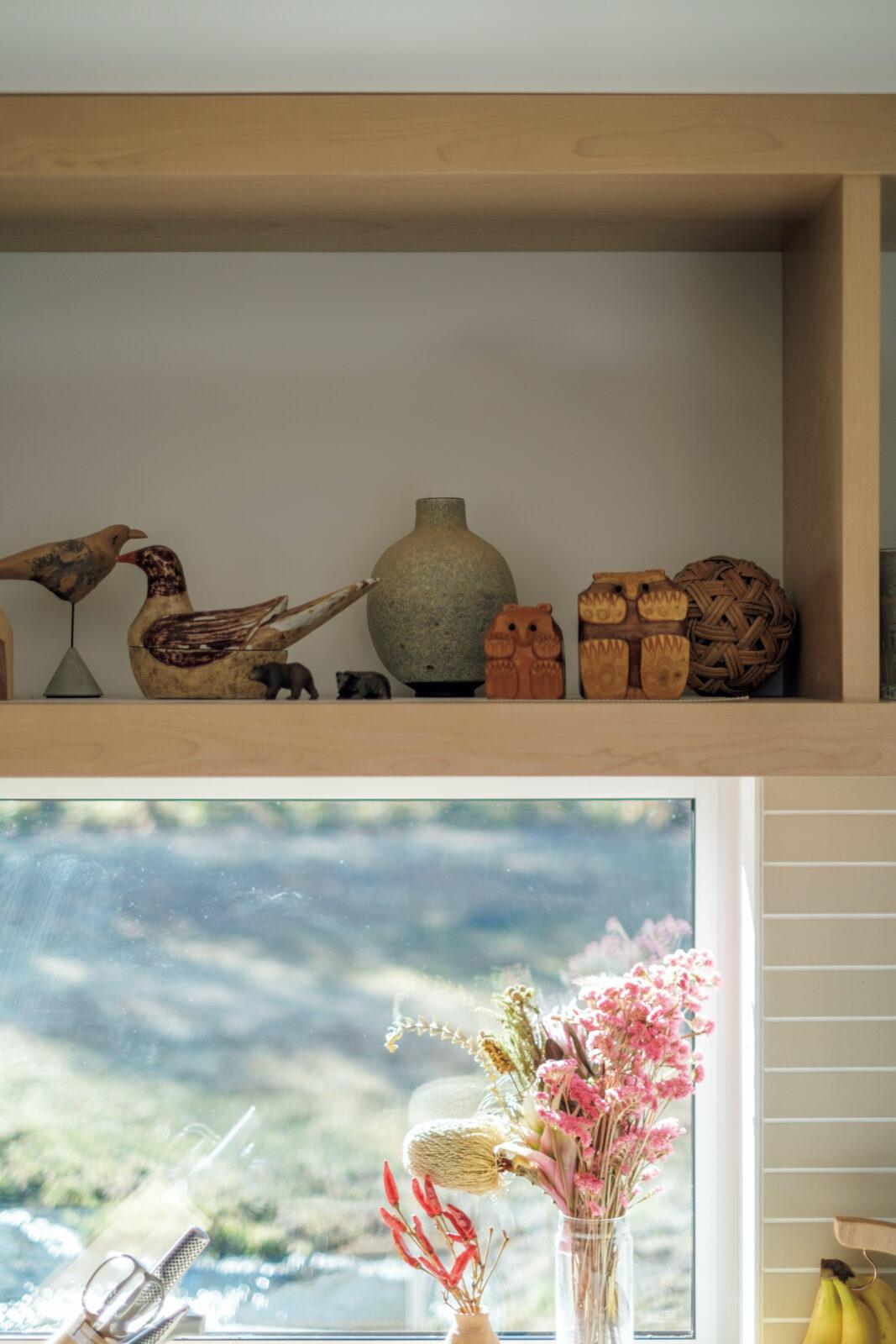 窓からの光がきれいなキッチン。シンク上の棚には、「置物で一番気に入っている」という十勝・足寄町の民芸品「どんころ熊」も。自然に囲まれたこの家に住んでから鳥の置物も増えた。