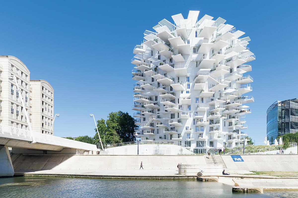 2019年、南仏モンペリエに完成した集合住宅〈ラルブル・ブラン/白い木〉。屋外で過ごすための広々としたテラスとパーゴラ(日陰棚)からは、旧市街の景色が見渡せる。©IWAN BAAN