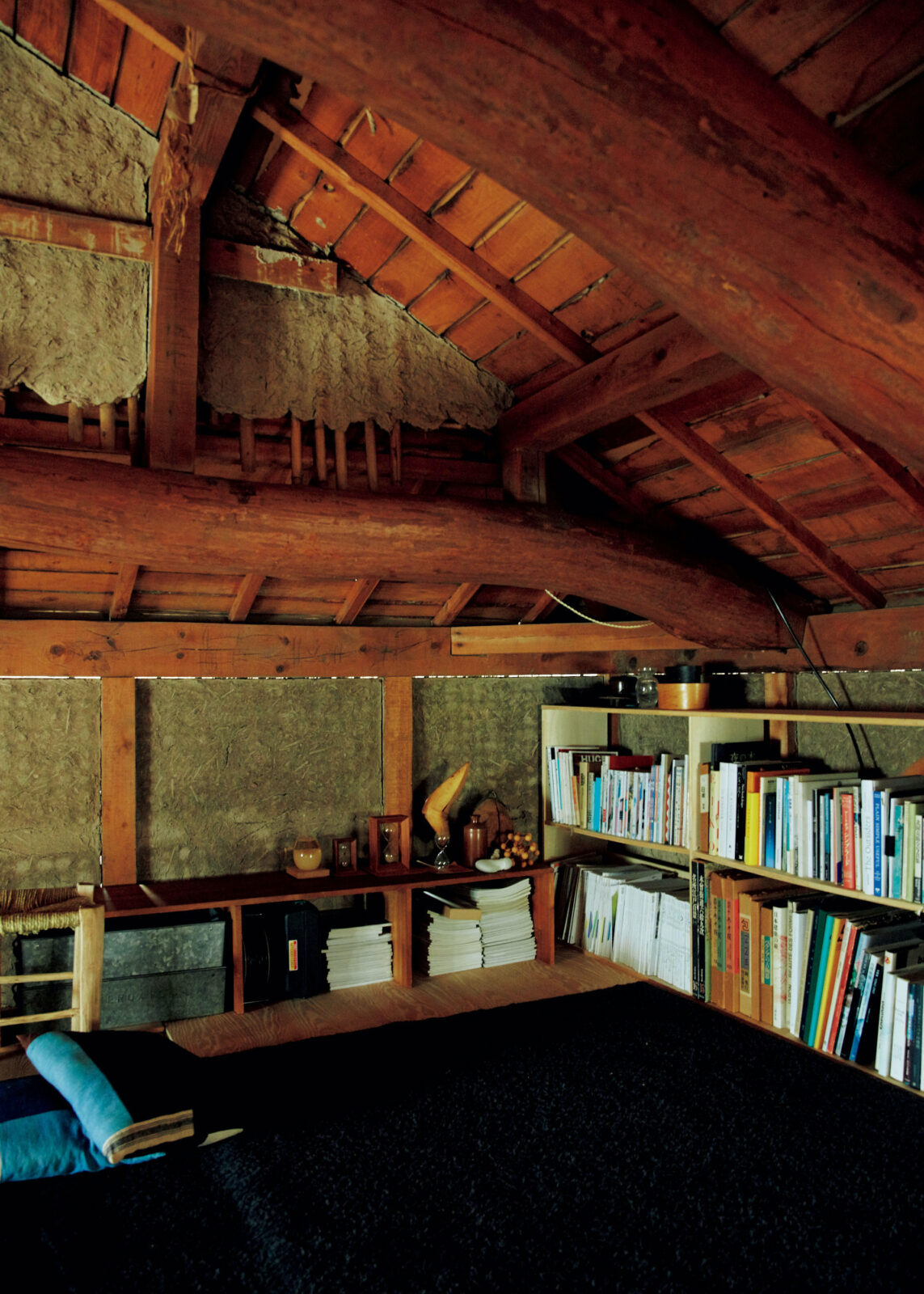 2階の天井裏。梁(はり)や土壁を現しにした、ほの暗い空間は、家族のライブラリースペース。住み始めて約6年。当初、天井裏は手つかずで、改修し切れなかった部分は住みながら少しずつ更新している。