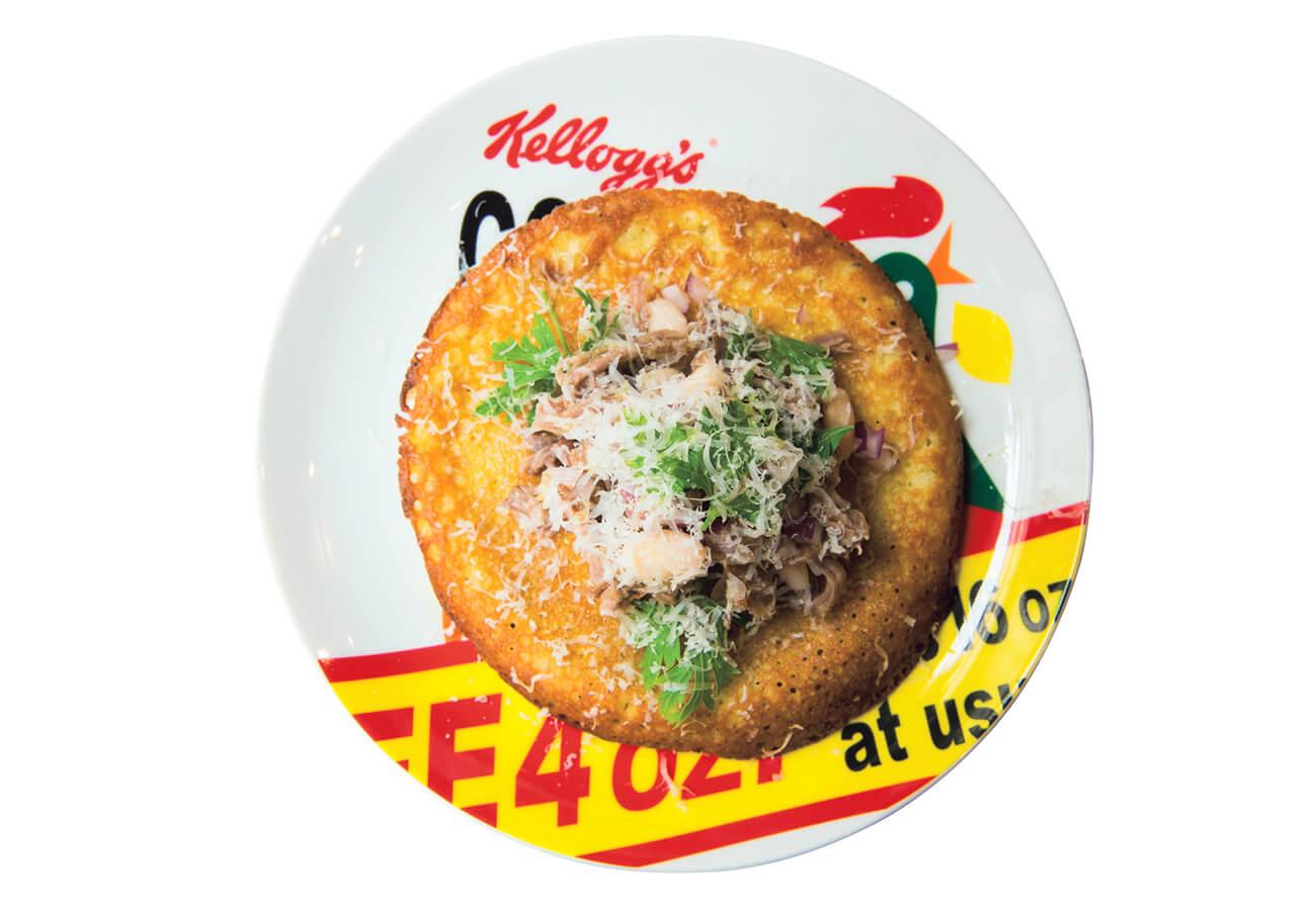 自家製コンビーフとファリナータ¥660。ヒヨコ豆の粉を焼いたファリナータがつまみに最高!お気に入りの〈ケロッグ〉の皿で。