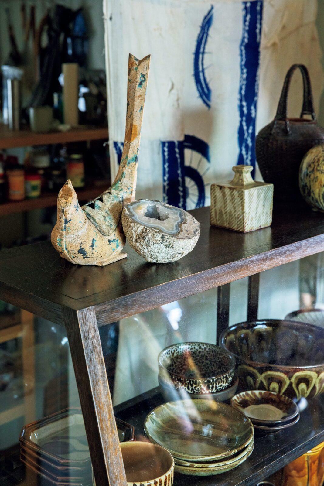 ダイニングとキッチンの空間を分けるショーケースは、この家用に〈テンポス〉で購入したもの。骨董市で掘り出した銅製の鳥は、中国のお香立てだった。右上の一輪挿しは人間国宝・島岡達三の民芸品で、妻・良子さんの祖母から譲り受けたもの。