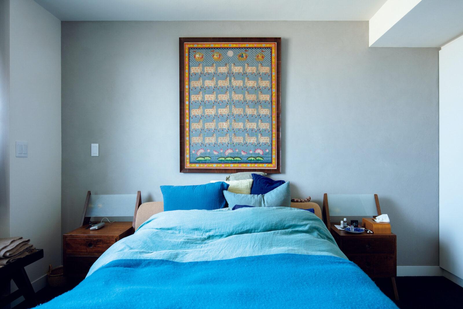 ビーチリゾートの静けさをイメージして、ブルーを基調にしたベッドルーム。壁は漆喰でグレーのグラデーションに仕上げた。部屋に合わせて額装したのは、インドの祈りでも使われる「ピクワイ」の絵画。